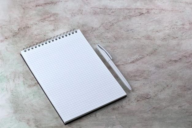ノートブックを開く空白のシートとペン大理石の背景をモックアップします。