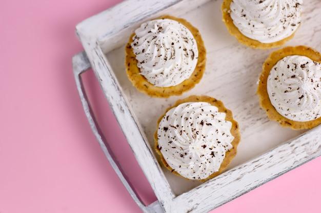 ホイップクリームピンクパステル調の背景を持つトップビューカップケーキ