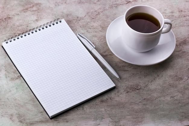 コーヒーカップと大理石の背景にノートブック
