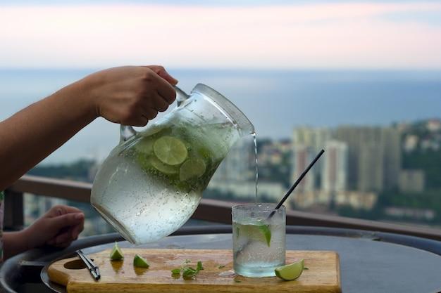 Холодный летний напиток с лаймом и мятой на балконе