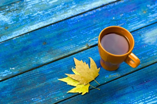 温かい飲み物と黄色の葉を持つ青い木の板