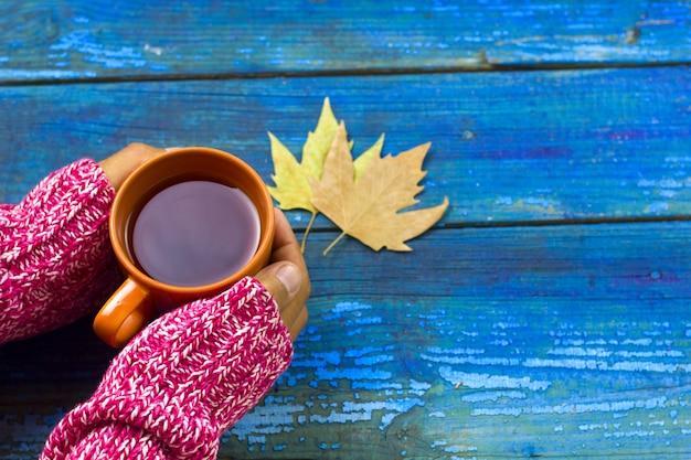 温かい飲み物と青い木の板に黄色の葉を持つ男の手
