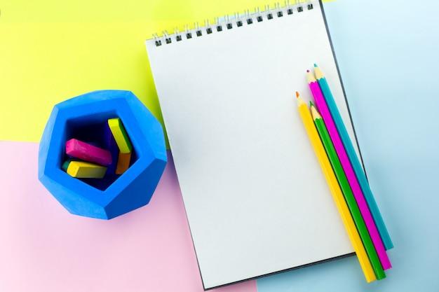Вид сверху яркий рабочий блокнот с пустым пространством для бумаги и яркими карандашами