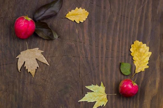 リンゴと乾燥した黄色の葉を持つ木製の秋の背景