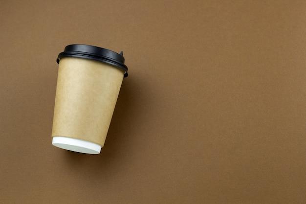 Одноразовые бумажные стаканчики на коричневом фоне