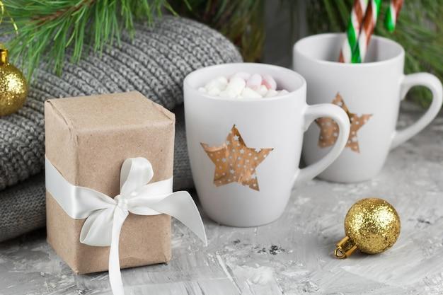 Подарочная коробка и милые чашки с маршмеллоу и леденцами под елкой