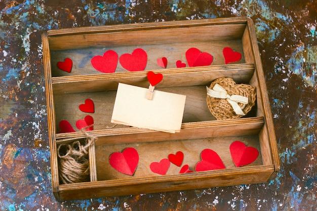 Деревянная коробка сверху с бумажными сердечками и подарком с красным бантом и пустым старым листом бумаги для надписи