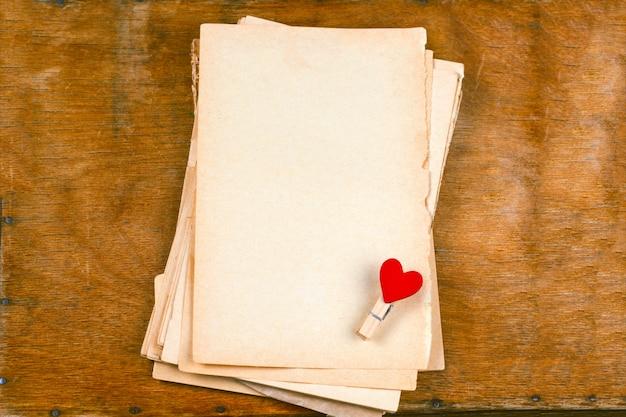 古い空の紙のシーツとクロストップビュー木製テーブルの上の布ピン聖バレンタインの日カードのために模擬