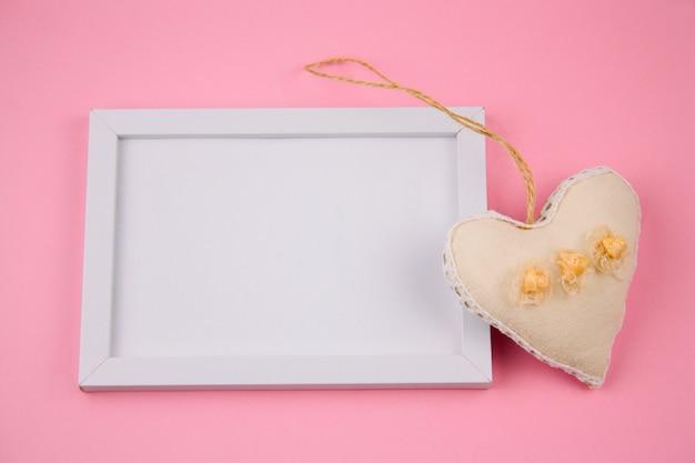 Белая рамка с местом для текста и тканевой игрушкой в форме сердца на розовом фоне
