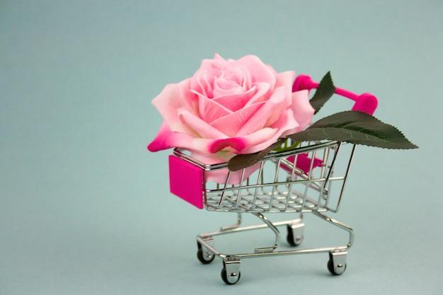 青色の背景にショッピングカートのピンクのバラ