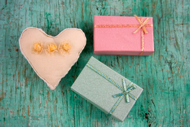Мягкая игрушка сердце и подарочные коробки потертый мятный зеленый деревянный фон
