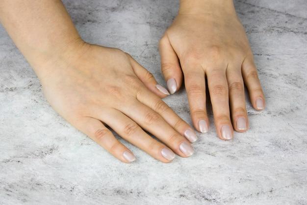 Крупным планом красивых женских рук с маникюром на мраморном столе