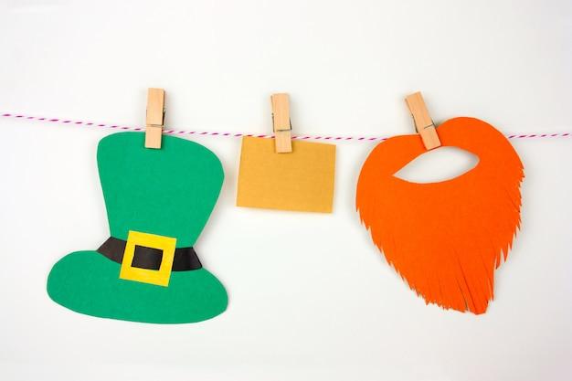 ビンテージの紙のメモ、紙の帽子、紙赤ひげと白い背景の上の洗濯はさみにシャムロックの葉