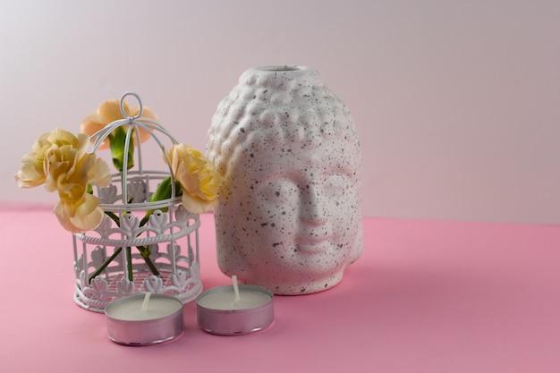 Белая керамическая статуэтка головы будды розовом фоне