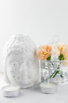 Белая керамическая статуэтка голова будды, декоративная клетка с цветами и свечами