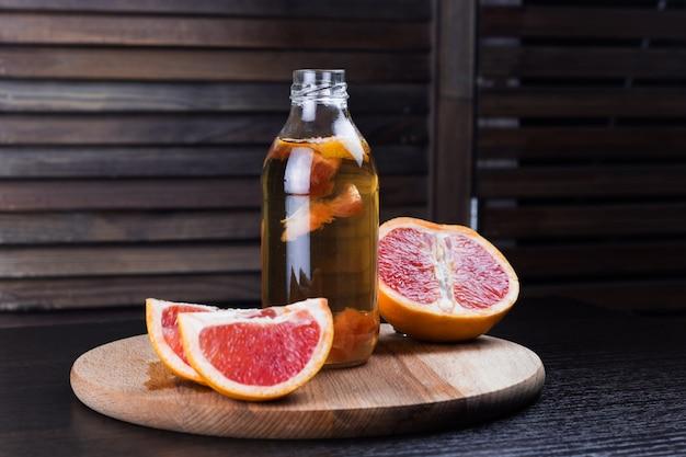 グレープフルーツの木製の背景とコンブチャ