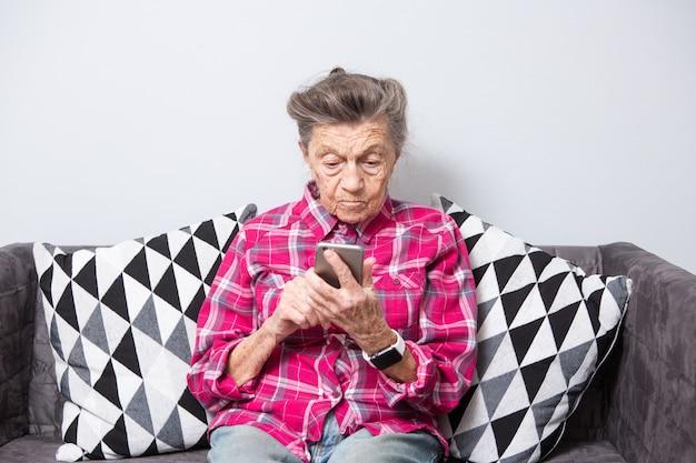 Старая седая кавказская женщина с морщинами сидит дома в гостиной на диване и использует мобильный телефон