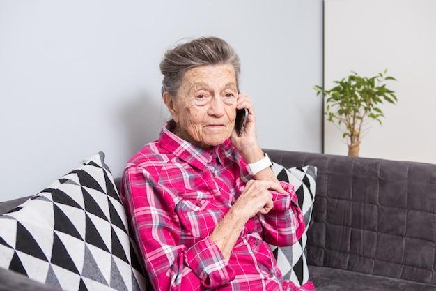 Зрелая счастливая радость улыбка активные седые волосы кавказские морщины женщина сидит дома в гостиной на диване