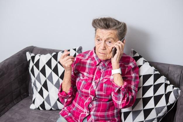 Пожилая бабушка с седыми волосами сидит дома на диване, используя телефон