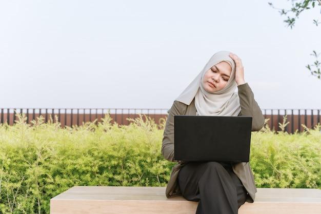 緑のスーツと公園でコンピューターに取り組んでいる若いアジアのイスラム教徒の女性。女性の頭痛と痛みを感じる。