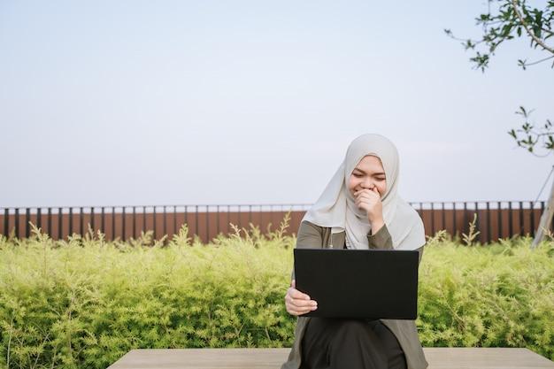 緑のスーツで若いアジアのイスラム教徒の女性を笑顔で公園でコンピューターに取り組んでいます。
