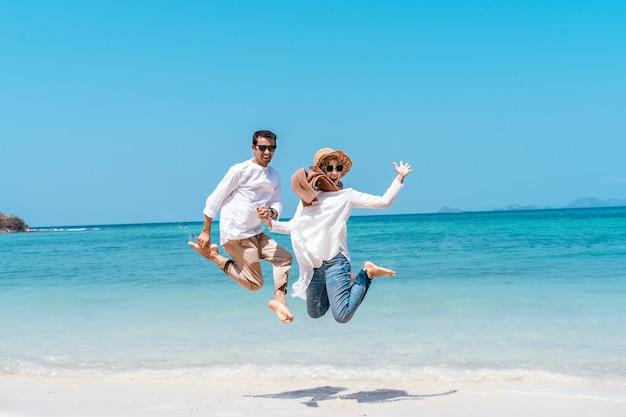 休暇の日にビーチで跳んで若いイスラム教徒のカップル。夏の時間