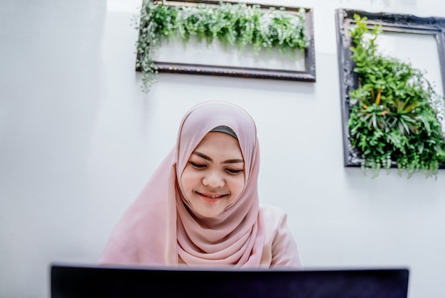 自信を持って若いイスラム教徒の女性がノートパソコンを入力します。白い部屋に座っている笑顔のアラブ女性。