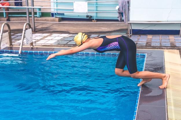 若い女性は、スイミングプールでスターティングブロックに低い位置で泳ぎます。