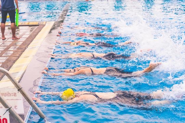 Девочки учатся плавать в бассейне.