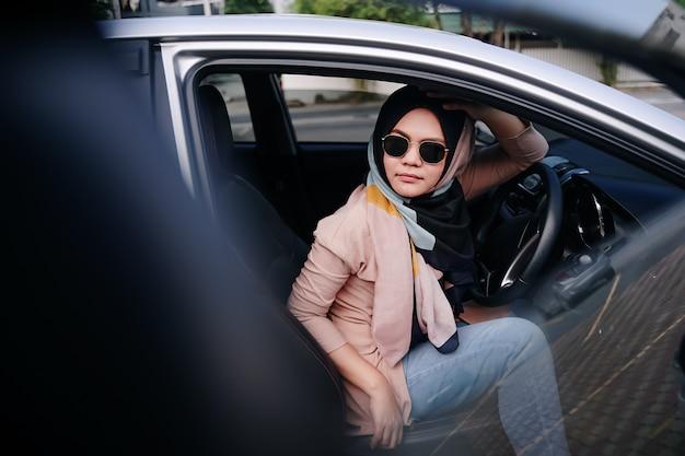 Внутренняя съемка автомобиля с женщиной, сидящей с закрытыми глазами на заднем сиденье.