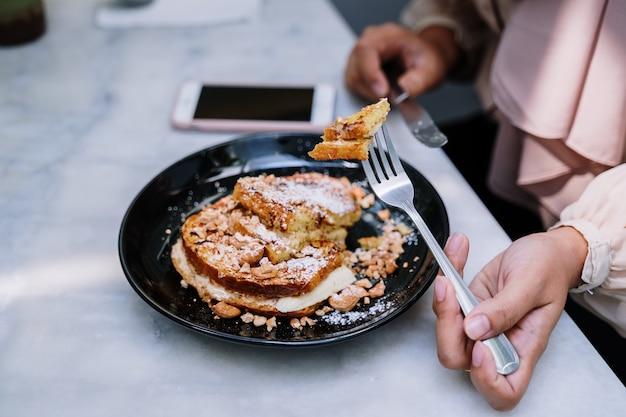 フォークを使って食べる女性の背景をぼかした写真のテーブルの上の黒い皿からさいの目に切ったフレンチトーストを食べる手。