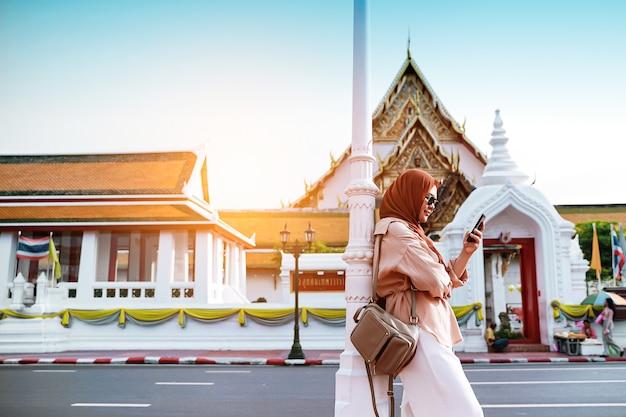 Задний взгляд мусульманской женщины турист гуляя в висок будды, азиатская женщина используя сотовый телефон в дороге. концепция путешествия.