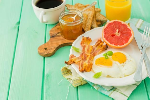 夏の朝食 - 卵、ベーコン、トースト、ジャム、コーヒー、ジュース