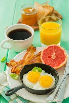 Летний завтрак - яйца, бекон, тост, джем, кофе, сок