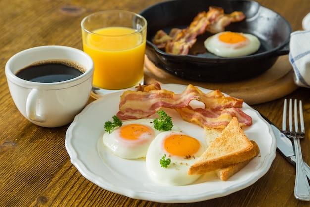Американский завтрак с солнечными яйцами, беконом, тостами, блинами, кофе и соком