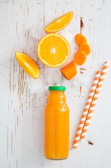 素朴な木の上のオレンジのスムージー