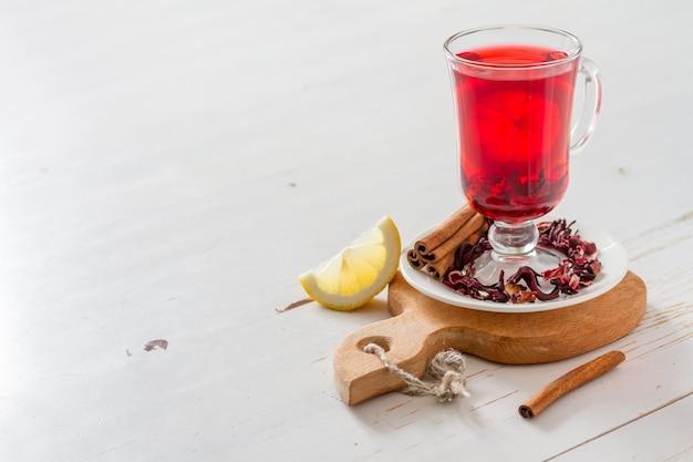白の木製の背景にカルカデ茶