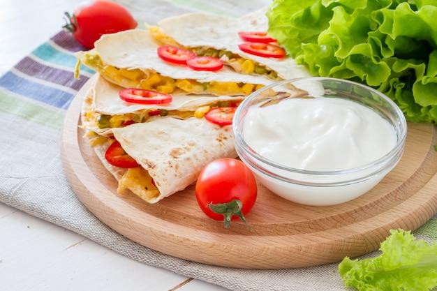 サワークリーム、サラダ、トマトのケサディーヤ