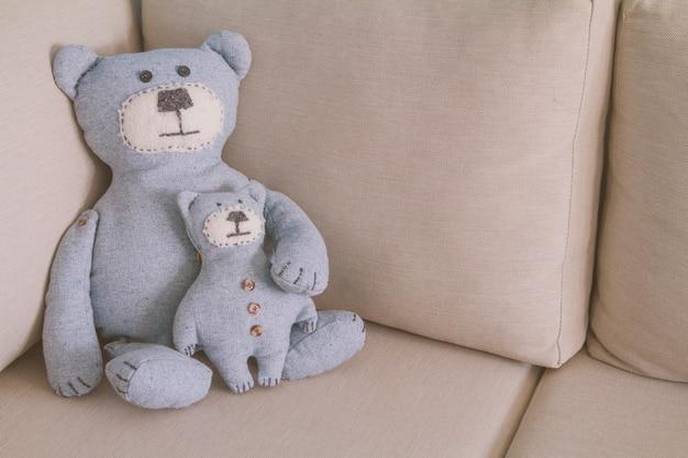 おもちゃのクマがソファーに座っていた