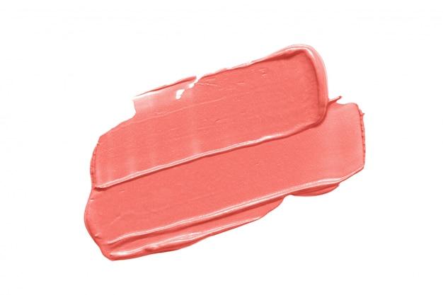 白で隔離されるトレンディなサンゴ色の口紅汚れ