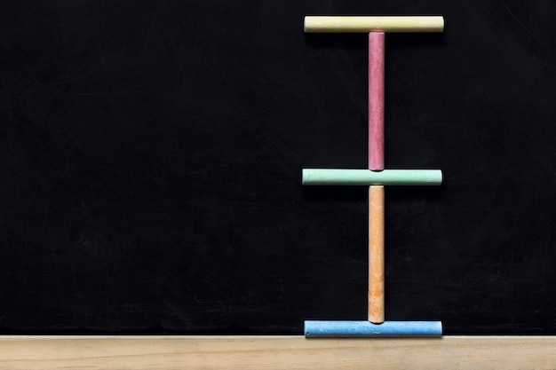 Черная классная доска с деревянной рамой и цветными мелками. вернуться к школьной доске фон