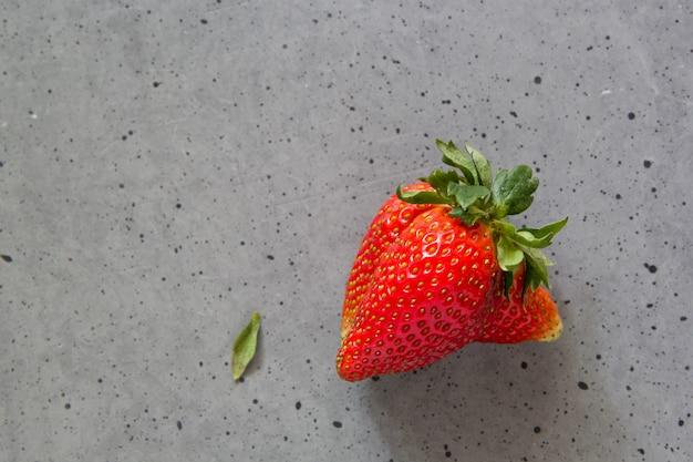 Уродливые плоды клубники на бетоне