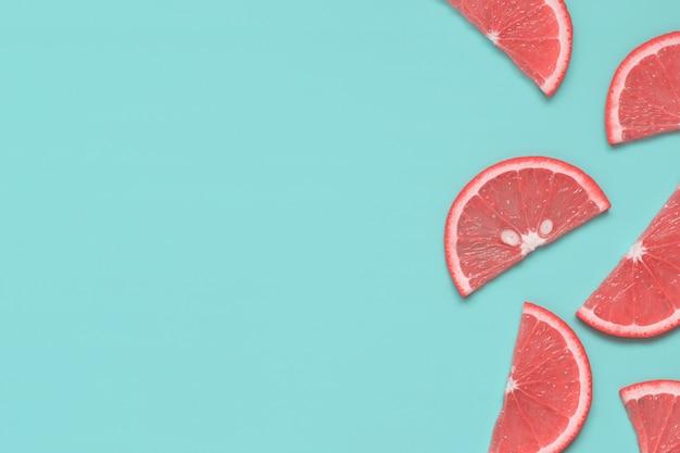 パステル調のターコイズブルーの背景に色肌の質感と柑橘系の果物のスライス