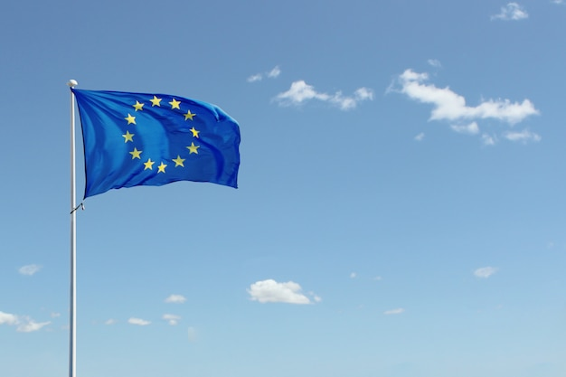 青い空を背景に手を振っている欧州連合の旗