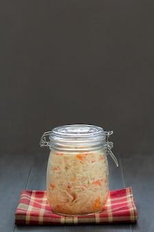 ザウアークラウト、発酵キャベツ、およびニンジンのサラダをガラスの瓶に入れます。