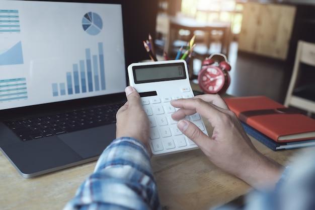 金融で働く男は電卓で計算し、オフィスの部屋でコンピューターのラップトップとドキュメントのデータグラフを使用します。