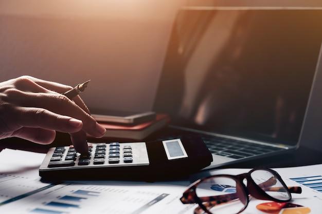 Бухгалтерский учет, бизнесмен используя калькулятор с компьтер-книжкой компьютера, бюджет и бумагу займа в офисе.