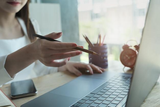 Молодые женщины, держа перо и используя компьютер ноутбук