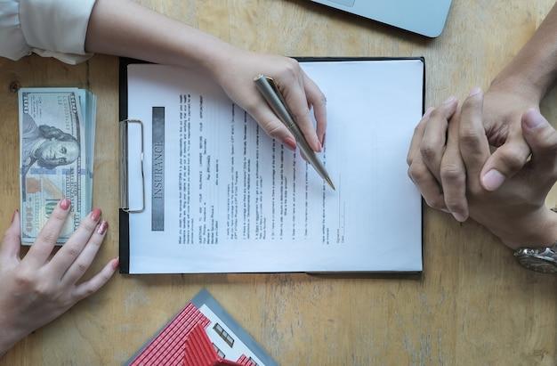 住宅保険を購入する契約に署名するために顧客と話し合う保険会社の役員。契約の概念。