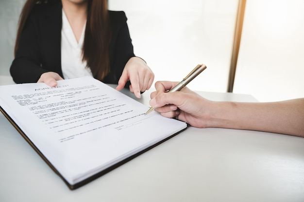ビジネスの女性とパートナーは、会議室で契約投資専門文書契約に署名します。